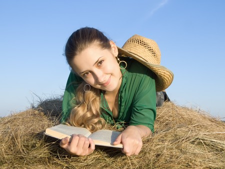 Girl reading at fresh hay from summer photo