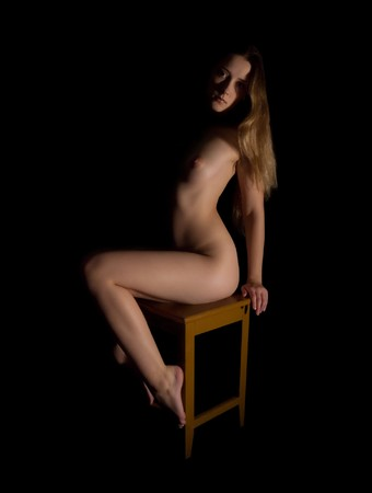 Sitting nudity girl.  Isolated on black background Stock Photo - 4336875