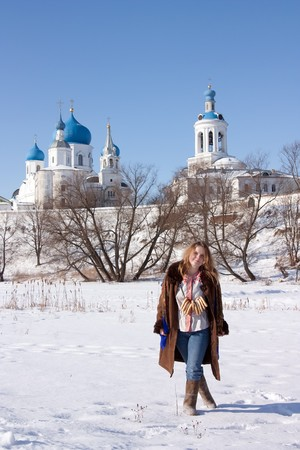 maslenitsa: girl in russian traditional clothes with round cracknel against  Russian landscape