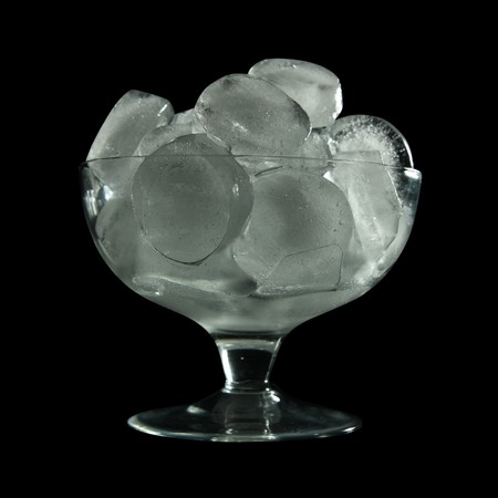 tall glass: ice cube in tall glass over black