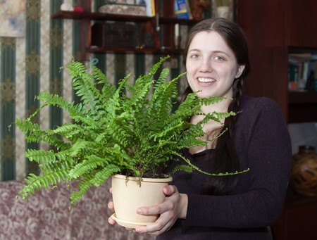 Attractive woman with fern flower in the pot at her home Stock Photo - 4523536