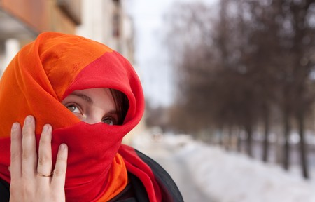 purdah: young beautiful woman in red purdah against street Stock Photo