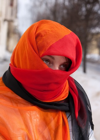 young beautiful woman in red purdah against street Stock Photo - 4553775