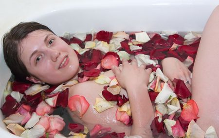 roseleaf: Young woman enjoys the rose-leaf in the bathtub. Stock Photo
