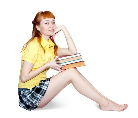 carroty girl in short skirt with books. Isolated on white