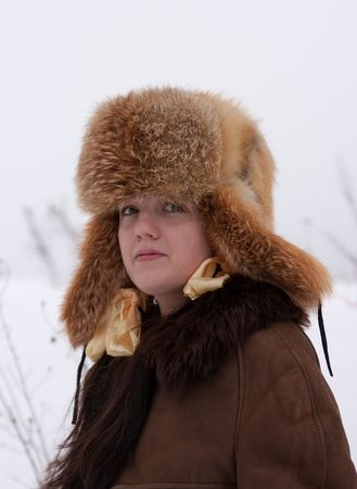young woman in sheepskin and hat with earflaps Stock Photo