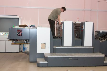 ofset: Printer working at his new offset machine