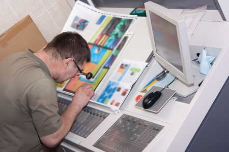 Printer checking a print run at table Stock Photo - 4704575