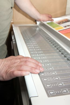 ofset: Workers hands on the electronic control panel of offset machine Stock Photo