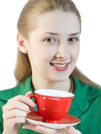 A girl in green blouse drinks tea from a red cup.  photo