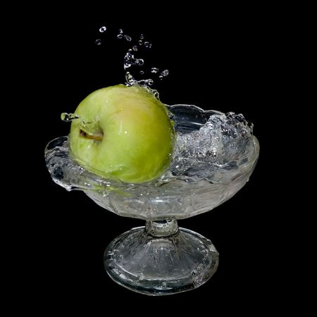 greeen: Apple falls into water over black background