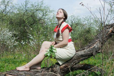 Sitting beautiful girl in a flowering garden photo