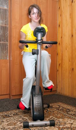 sportswoman: Young woman working out on exercise bike at the gym. Stock Photo