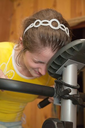 weariness: weariness girl  in yellow sportswear exercising on exercise bike Stock Photo