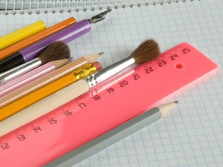 pencils and brushes on squared sheet of a copybook Stock Photo - 4985234