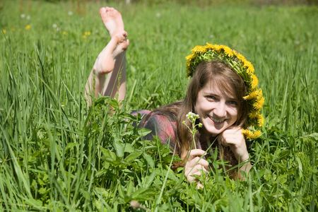 long-haired teen girl in a chaplet lying from meadow Stockfoto