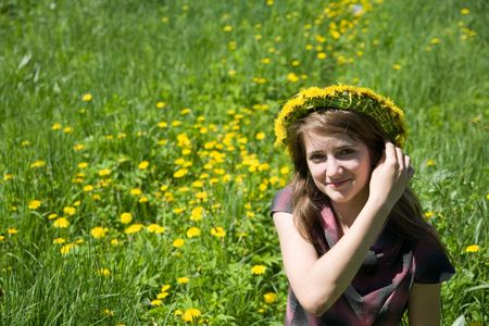 long-haired teen girl  in a chaplet against a meadow Stockfoto