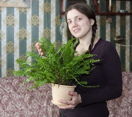 brake fern: Attractive woman with fern flower in the pot at her home