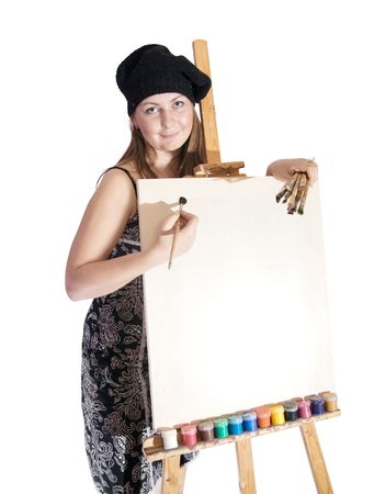 Girl with brushes near blank white canvas. Isolated over white photo