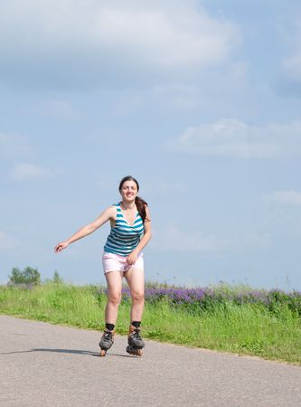 young female rollerskating on asphal road against nature photo