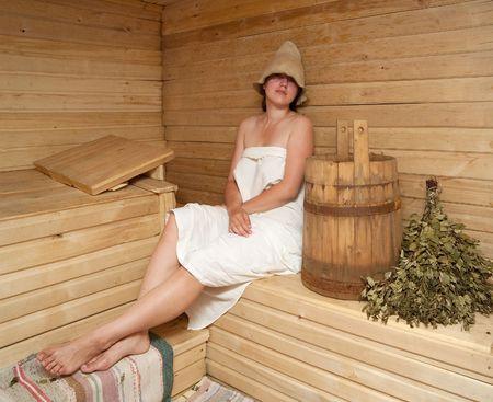 Young woman is taking a steam-bath at sauna bath photo
