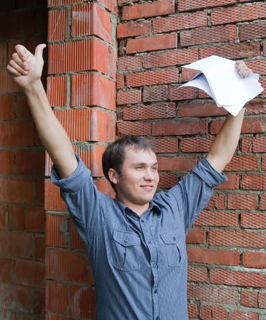Happy builder with documents against  the brick wall photo