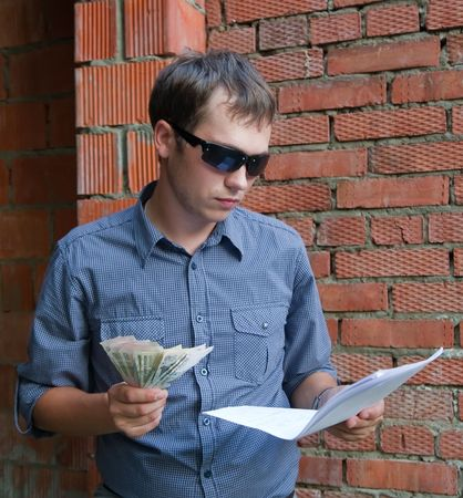 tasker: foreman with documents and money  against  the brick wall