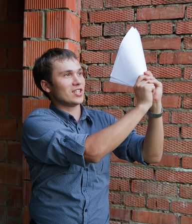 tasker: Happy foreman with documents against  the brick wall