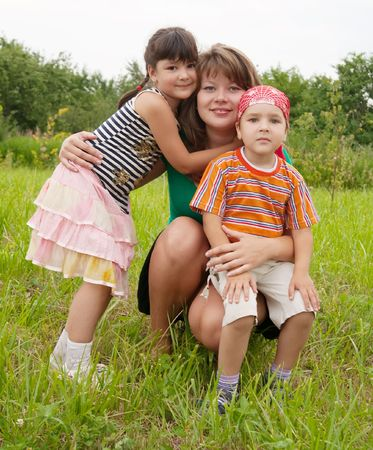 Happy mother with her children sit in grass Stock Photo - 5312509