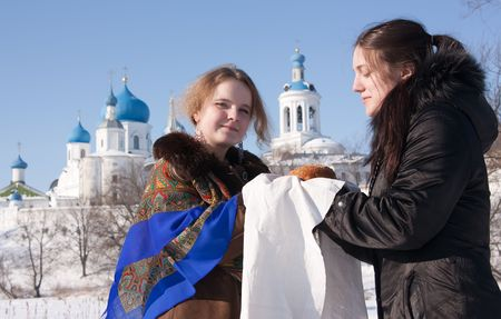 A girl in russian traditional kerchief  gives loaf a tourist photo