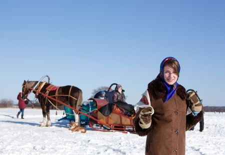 horse sleigh: girl in russian traditional clothes against  winter landscape