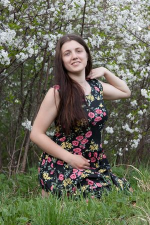 portrait of young woman in the blossoming garden photo