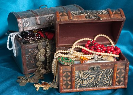 valuables: Two wooden treasure chests with valuables on blue textile Stock Photo