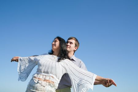 portrait of a young man and his girlfriend stretching their hands together  photo