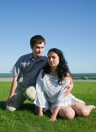 Loving young couple at the park against blue sky photo