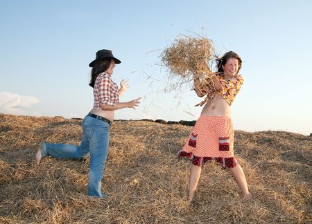 Country girls play with hay  against sky  photo