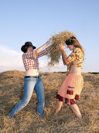 Country girls play with hay  against sky  Stock Photo - 5428101