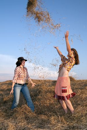 Happy girls throwing hay on against sky  photo