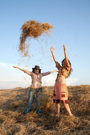 Happy girl throwing hay on background of the sky  photo