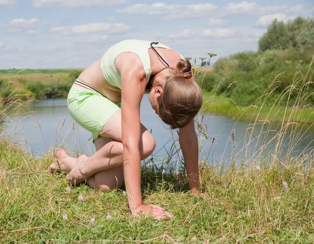 Beautiful young girl practicing yoga  against river Stock Photo - 5437603