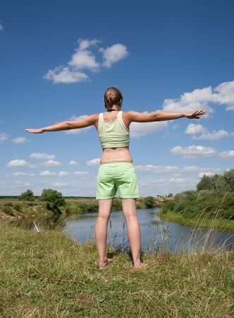 Beautiful young girl practicing yoga  against blue sky Stock Photo - 5437599