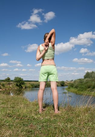 Beautiful young girl practicing yoga  against river Stock Photo - 5437593