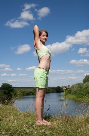 Beautiful young girl practicing yoga  against river Stock Photo - 5437604