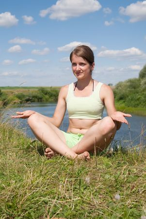 Beautiful young girl practicing yoga against river Stock Photo - 5437613