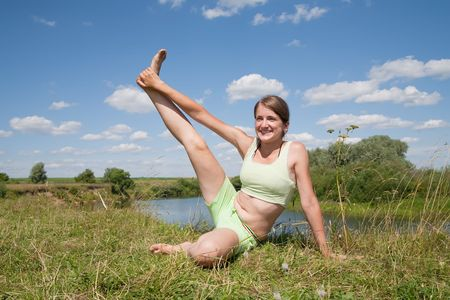 Beautiful young girl practicing yoga  against blue sky Stock Photo - 5437614