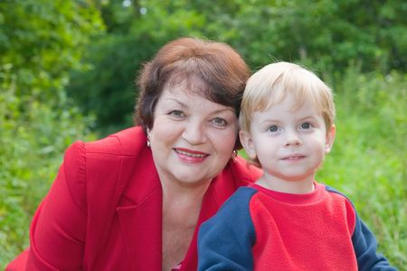 Portrait of happy grandmother with child against nature photo
