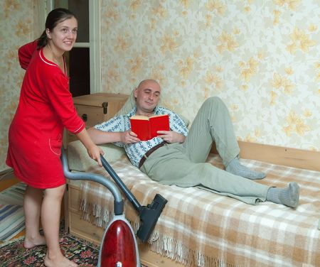 Woman running the vacuum cleaner against her husband photo