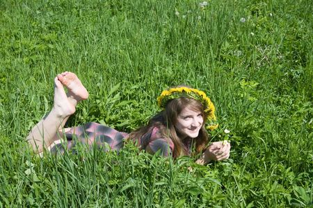 barefoot teen girl in a chaplet lying from meadow photo