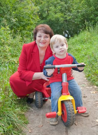 grandmother with boy on tricycle at nature photo