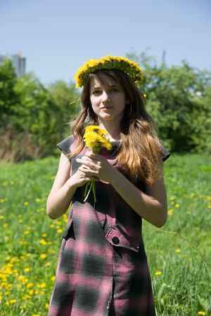 teener: long-haired teen girl  in a chaplet against a meadow Stock Photo